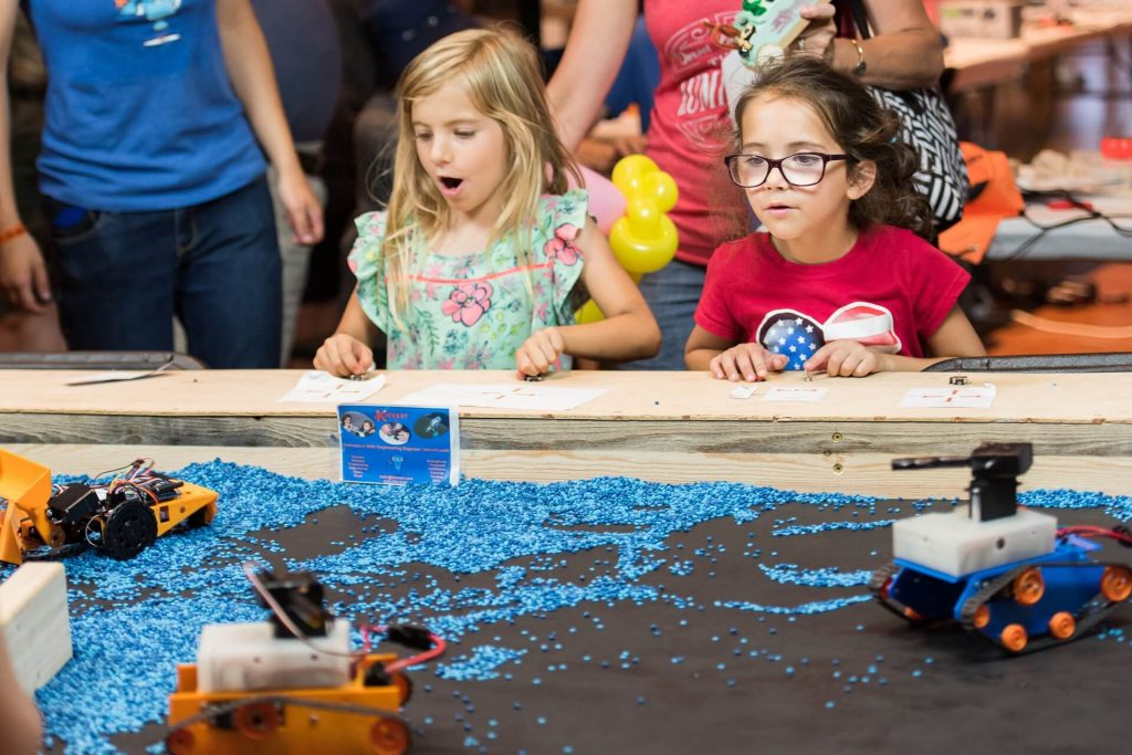 Girls learn STEM driving construction robots made by Kinvert STEM students
